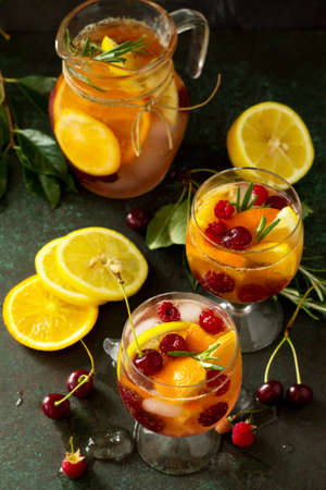 Homemade refreshing wine sangria or punch with fruits. Sangria cocktails with fresh fruits, berries and rosemary on dark a stone or slate background.