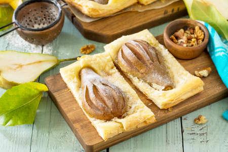 Postre de verano. Pastel casero de hojaldre con pera y relleno de crema de nueces una mesa de madera rústica. Foto de archivo