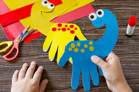 The child holds Father's day or birthday gift - card dinosaur. Handmade. Project of children's creativity, handicrafts, crafts for kids.