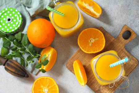 Refreshing juice made of orange, cold drink on a stone or slate background. Concept fresh vitamins. Rustic style. Flatlay top view. Archivio Fotografico