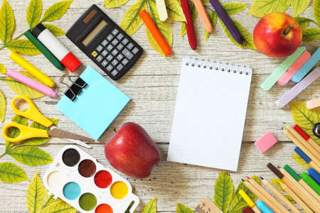 Back to school. Flatlay background. Table with autumn leaves, note pad, apple  and school supplies. Free space for your text.