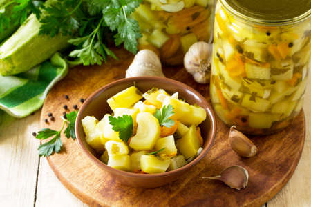 Homemade preserving. Pickled Zucchini Salad with vegetables on the kitchen wooden background. Imagens