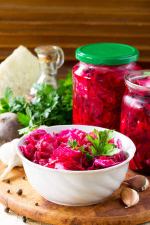Homemade preserving. Fermented food. Salad Cabbage with Beetroot on the kitchen wooden background.