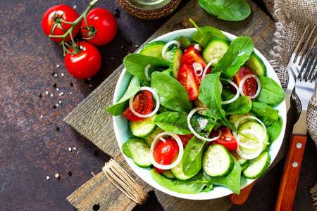 Spuntino vitaminico. Insalata con verdure fresche e spinaci su un tavolo di pietra o cemento scuro. Spazio libero per il tuo testo. Sfondo piatto vista dall'alto.