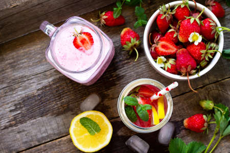 Dietary breakfast for summer time, vegan food concept. Fresh Strawberry milkshake and strawberry lemonade on rustic wooden table. Top view flat lay background. Copy spase.