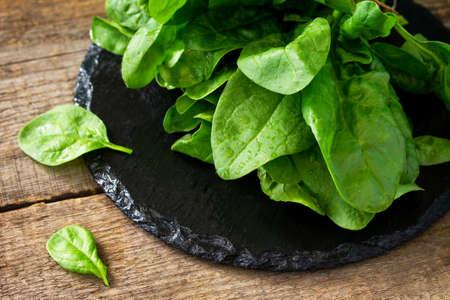 Frische Salatspinatblätter auf dem Küchentisch aus Holz.