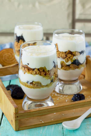 Vegan Dessert with whipped cream, nuts, oatmeal, prunes and sesame in glass glasses on a wooden rustic table. Free space for your text.