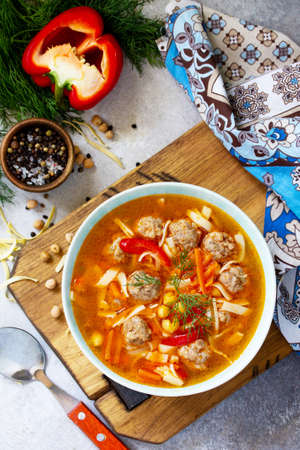Homemade Hot Soup with pasta, turkey meatballs and Peas Chickpeas. Eastern cuisine. The concept of healthy eating. Top view flat lay background. Standard-Bild