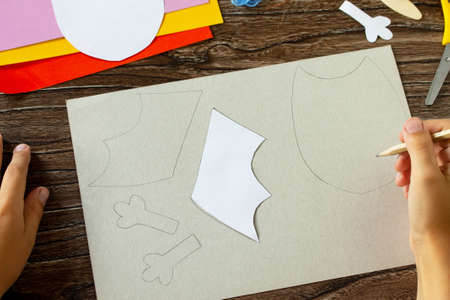 The child draws the details of Dracula bat for Halloween. Children's art project, craft for children.