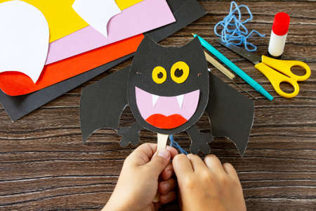 The child plays of dracula bat for Halloween. Children's art project, craft for children.