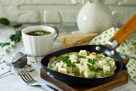 Breakfast background. Fried eggs with spinach, feta cheese on stone table. Free space for your text. Imagens