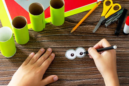 Child draws details Paper Roll Pencil Holder the new school year. Welcome back to school. Children's Art Project, needlework, crafts for kids.
