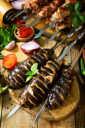 Barbecue menu. Grilled eggplant with bacon, grilled sausages and Grilled meat skewers on rustic wooden table.