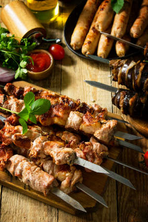 Barbecue menu. Grilled meat skewers, grilled sausages and grilled eggplant with bacon on rustic wooden table.