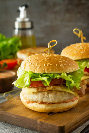 Delicious grilled burgers, hamburger sandwich with cutlet of chicken meat, melted cheese, tomatoes and bacon on a wooden board.Free space for your text.