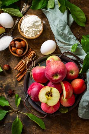 Apple baking seasonal concept. Ingredients for apple pie (red apple, flour, eggs, anise, sugar, hazelnut and cinnamon) on a rustic wooden table. Top view flat lay.