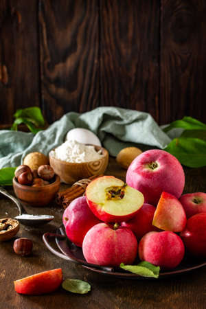 Apple baking seasonal concept. Ingredients for apple pie (red apple, flour, eggs, anise, hazelnut, sugar and cinnamon) on a rustic wooden table. Free space for your text.