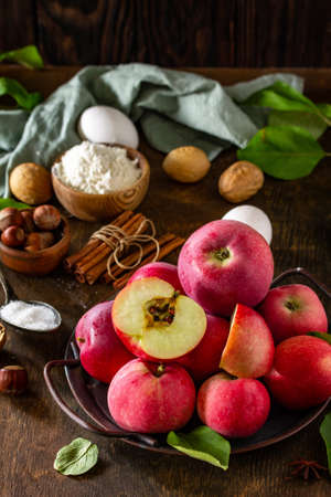 Apple baking seasonal concept. Ingredients for apple pie (red apple, flour, eggs, anise, sugar and cinnamon) on a rustic wooden table. Imagens