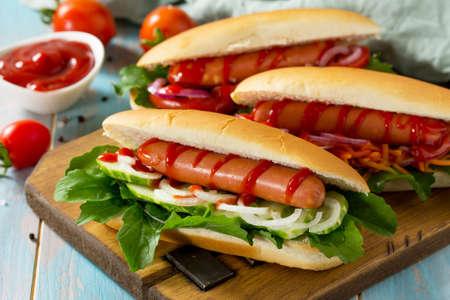 Comida rápida americana tradicional. Perrito caliente a la parrilla con verduras frescas en la mesa de madera.