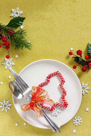 Christmas background. Christmas decoration table. Festive plate and cutlery with decor on festive table. Top view flat lay. Free space for your text. Banco de Imagens