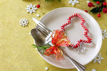 Christmas background. Christmas decoration table. Festive plate and cutlery with decor on festive table. Free space for your text.