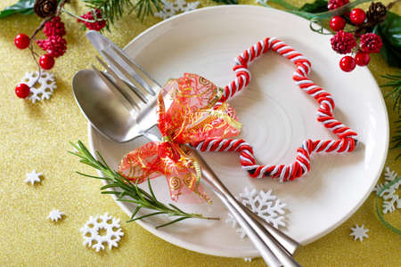 Christmas background. Christmas decoration table. Festive plate and cutlery with decor on festive table.