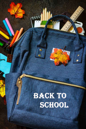 Back to school concept. School supplies with blue backpack on table. Top view flat lay.
