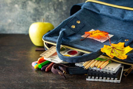 Back to school concept. School supplies with blue backpack on table. Free space for your text.