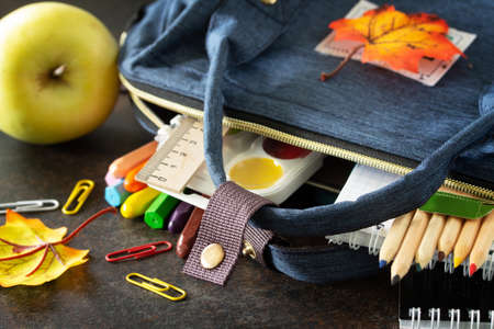 Back to school concept. School supplies with blue backpack on table.