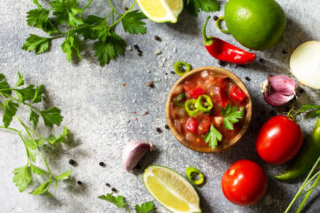 Traditional Latin American mexican salsa sauce with ingredients on a light stone table. Top view flat lay.