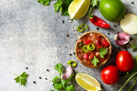 Traditional Latin American mexican salsa sauce with ingredients on a light stone table. Top view flat lay. Free space for your text.