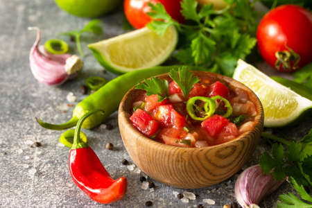 Traditional Latin American mexican salsa sauce with ingredients on a light stone table. Stockfoto