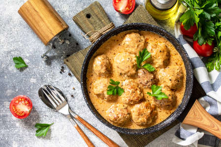 Meatballs in sour cream and tomato sauce in a frying pan on stone table. Top view flat lay.
