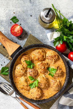 Meatballs in sour cream and tomato sauce in a frying pan on stone table. Top view flat lay. Free space for text. Фото со стока
