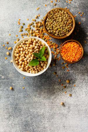 Alimentation saine, régime, source de protéines végétaliennes concept. Cru de légumineuses (pois chiches, lentilles rouges, lentilles canadiennes). Vue de dessus à plat. Espace libre pour le texte.