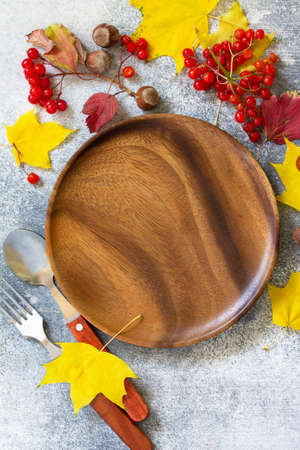 Autumn table setting. Thanksgiving or autumn harvest table setting with silverware and frame of leaves. Top view flat lay. Free space for text.