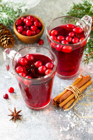 Christmas drinks. Hot winter drink with cranberries and cinnamon on a light stone table. Free space for your text.