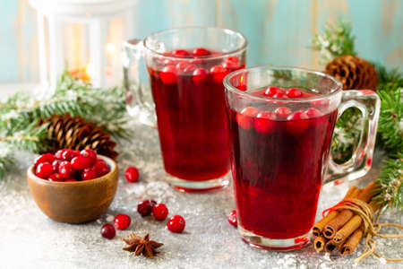 Christmas drinks. Hot winter drink with cranberries and cinnamon on a light stone table. Stok Fotoğraf