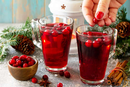 Christmas drinks. Female hand holding of Hot winter drink with cranberries and cinnamon on a light stone table.