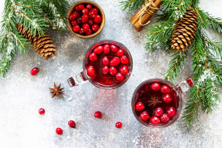 Christmas drinks. Hot winter drink with cranberries and cinnamon on a light stone table. Top view flat lay.