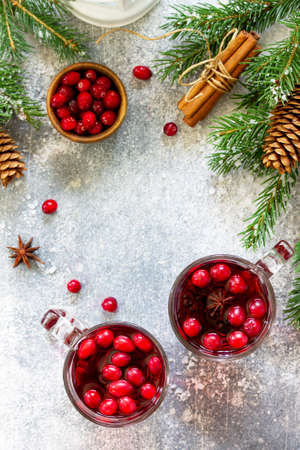 Christmas drinks. Hot winter drink with cranberries and cinnamon on a light stone table. Top view flat lay. Free space for your text.