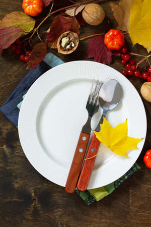 Autumn rustic table. Thanksgiving or autumn harvest table setting with rustic silver on a wooden table. Top view of a flat lay.