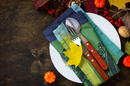 Autumn rustic table. Thanksgiving or autumn harvest table setting with rustic silver on a wooden table. Top view of a flat lay. Free space for your text.