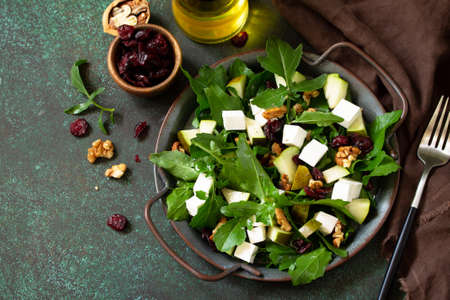 Diet menu, vegan food. A healthy salad with arugula, feta cheese, pear, nuts, dried cranberries and vinaigrette sauce on a stone table.  Free space for your text.