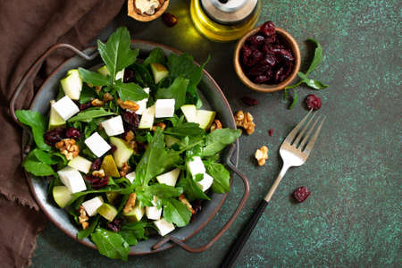 Diet menu, vegan food. A healthy salad with arugula, feta cheese, pear, nuts, dried cranberries and vinaigrette sauce on a stone table. Top view. Free space for your text. Stock Photo