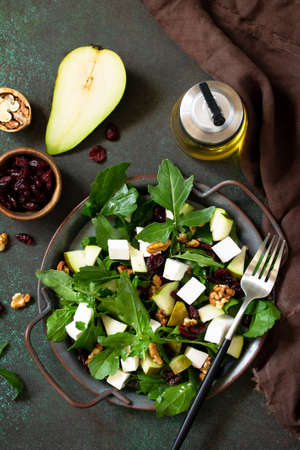 Diet menu, vegan food. A healthy salad with arugula, feta cheese, pear, nuts, dried cranberries and vinaigrette sauce on a stone table. Top view.