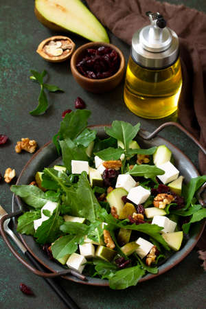 Diet menu, vegan food. A healthy salad with arugula, feta cheese, pear, nuts, dried cranberries and vinaigrette sauce on a stone table.