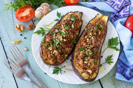 Healthy dinner. Snack. Stuffed with minced meat and vegetables eggplant on wooden table.