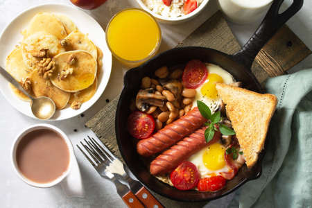 Keto breakfast: fried eggs, sausages, beans, bacon, mushrooms, grilled toasts, orange juice, cottage cheese, pancakes and cocoa on a light stone table. Top view flat lay background.