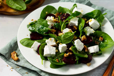 Vitamin snack. Salad with spinach, feta cheese, beetroot and walnut, vegetable oil sauceon a concrete table. Reklamní fotografie